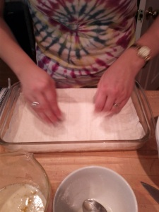 The first layer of phyllo dough, with Erin adding butter.